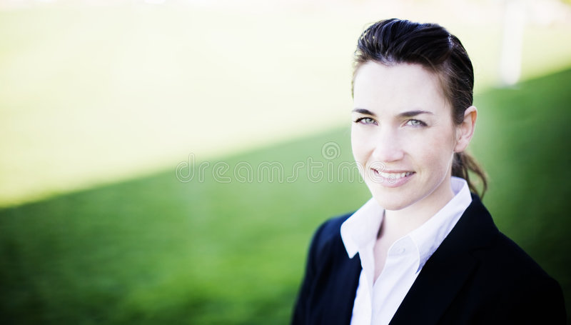 Businesswoman smiling. While wearing a business suit standing outside in the grass and sunshine stock images
