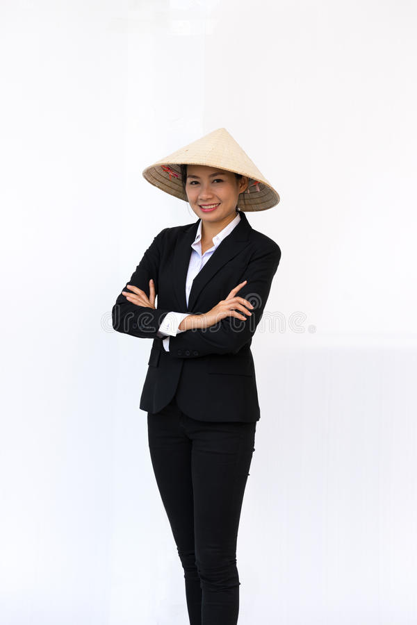Businesswoman smiling in black suit and hat standing arms crossed royalty free stock photography