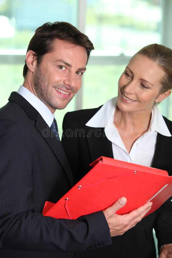 Businesswoman smiling at businessman royalty free stock photos