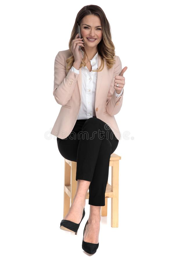 Businesswoman speaking on the phone makes thumbs up sign stock photos
