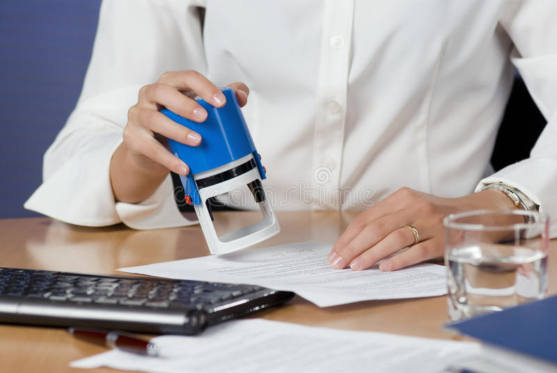 Businesswoman stamping documents stock photo