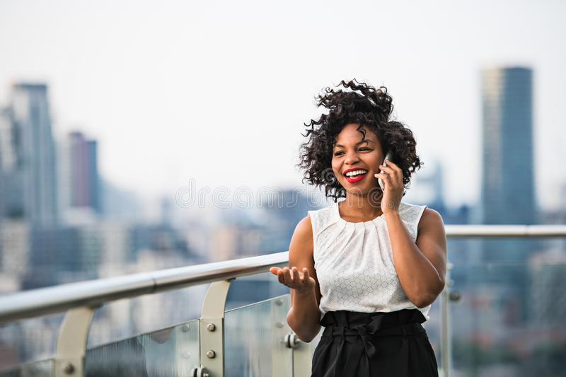 A businesswoman standing against London view panorama, making a phone call. royalty free stock images