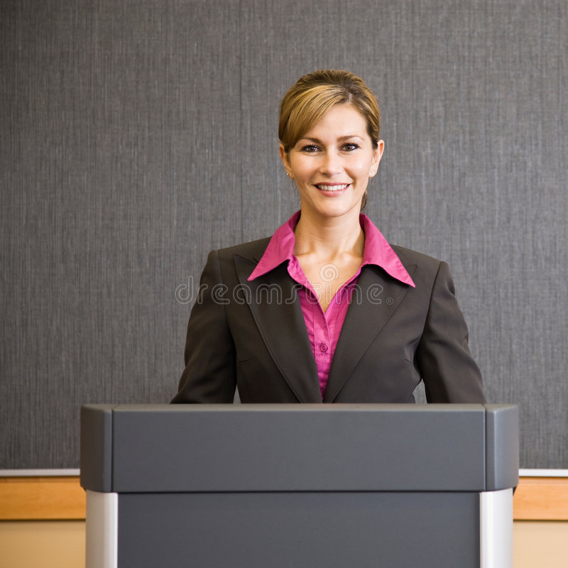 Businesswoman standing behind podium stock image