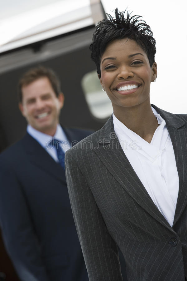 Businesswoman Standing With Colleague At Airfield stock photo