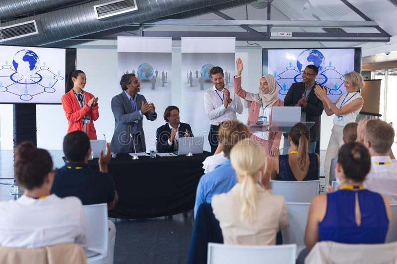 Businesswoman standing with colleagues and speaks in a business seminar. Front view of pretty mixed-race businesswoman in hijab standing with diverse colleagues royalty free stock photo