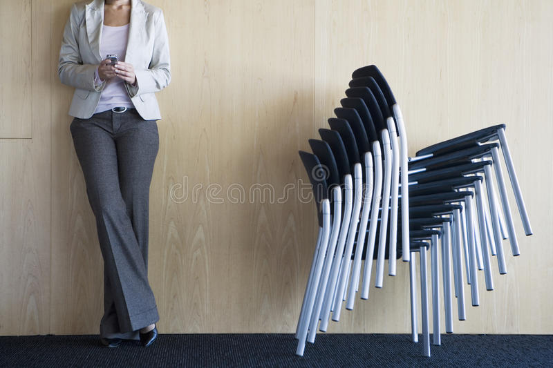 Businesswoman standing in conference room beside stack of chairs, holding mobile phone, low section royalty free stock images