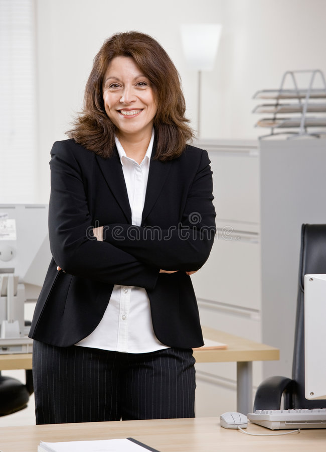 Businesswoman standing at desk in office royalty free stock photos