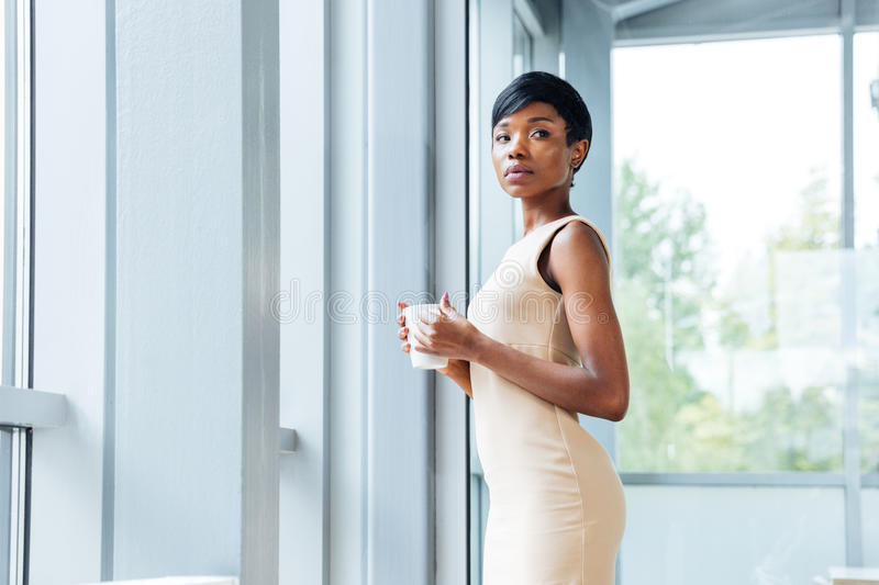 Businesswoman standing and drinking coffee in office royalty free stock images