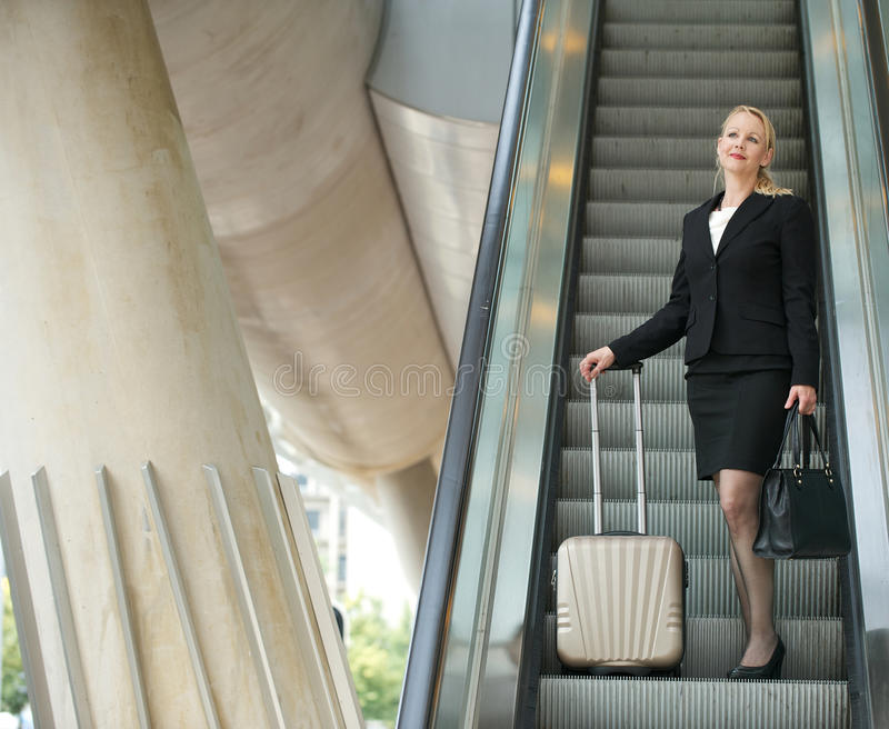 Download Businesswoman Standing On Escalator With Luggage Stock Photo - Image: 32626034