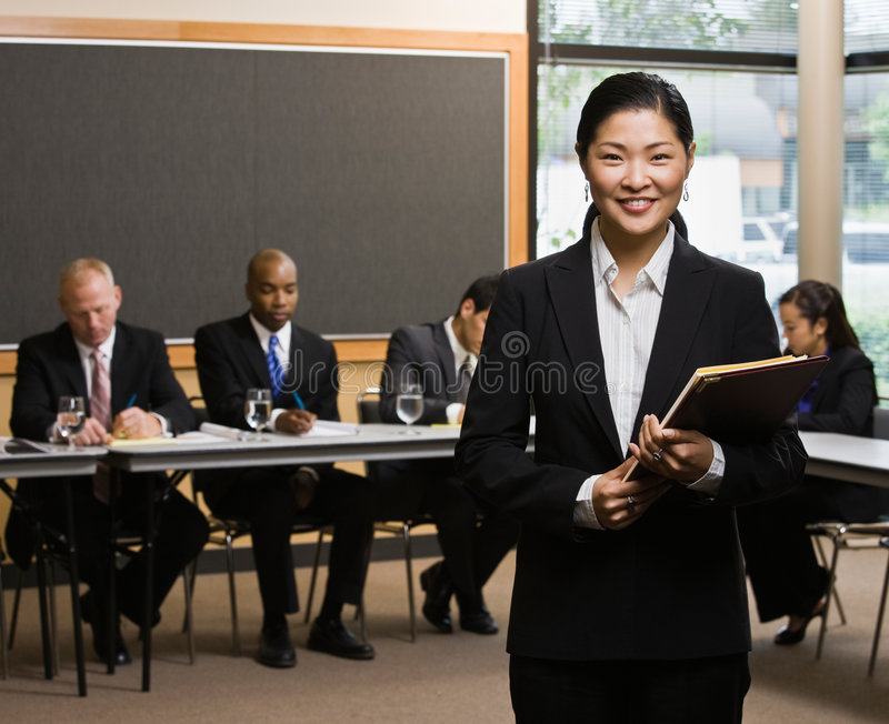 Businesswoman standing in front of co-workers royalty free stock image