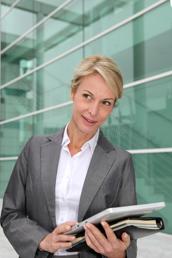 Businesswoman standing in front of house building stock images