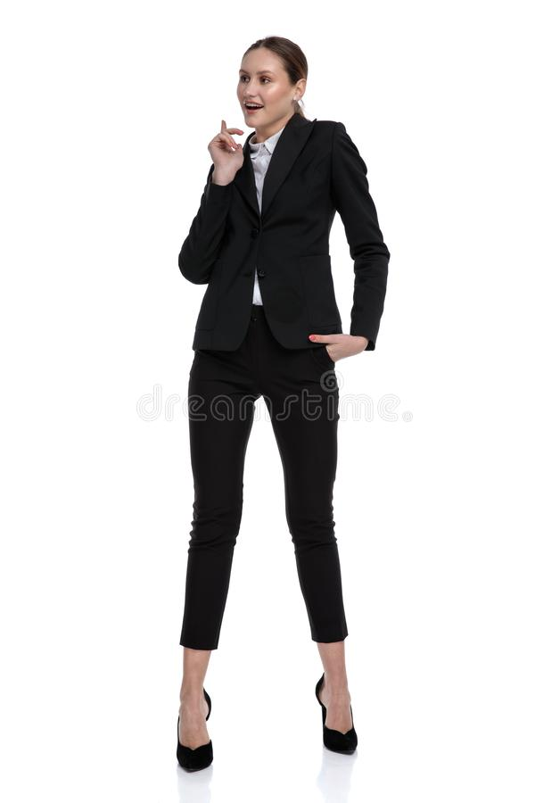 Businesswoman standing with hand in pocket and figuring something out. Attractive formal businesswoman wearing black suit standing with hand in pocket and stock photos