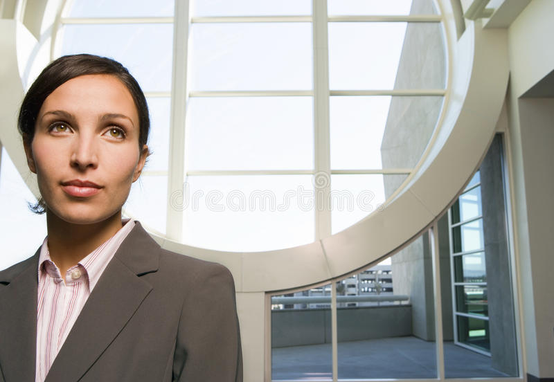 Businesswoman standing in lobby, near large circular window, smiling, front view stock photo