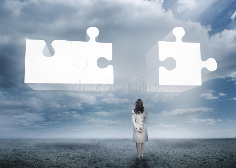 Businesswoman standing looking at jigsaw puzzle stock photography