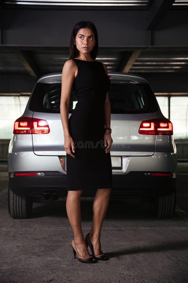 Businesswoman standing near her car on underground parking stock photography