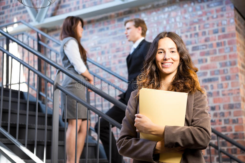 Businesswoman standing near staircase with documents royalty free stock image