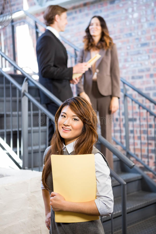 Businesswoman standing near staircase with documents stock image