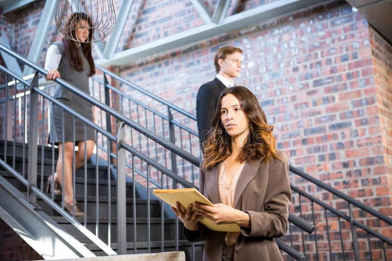 Businesswoman standing near staircase with documents stock photos
