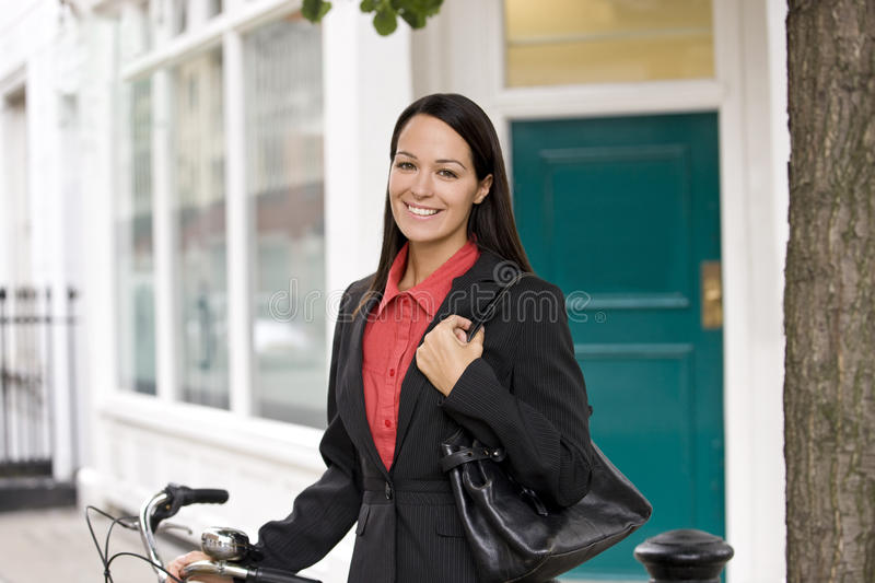 A businesswoman standing next to her bicycle stock images