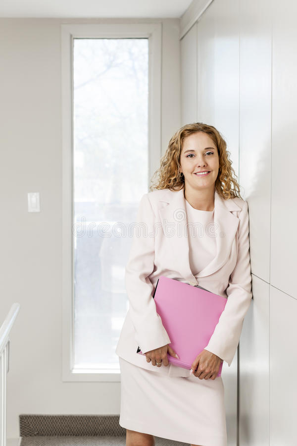 Businesswoman standing in office hallway royalty free stock photos