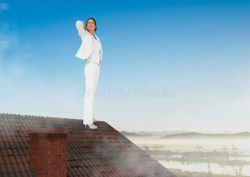 Businesswoman standing on Roof with chimney and landscape royalty free stock image