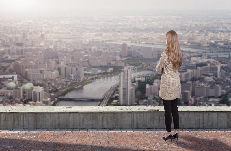 A businesswoman standing on roof looking at city stock photo