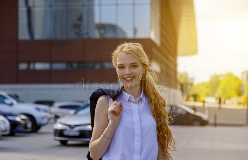 Businesswoman standing on street with jacket over shoulder. Businesswoman in formal clothes standing on street with jacket over shoulder. European woman walking stock photos