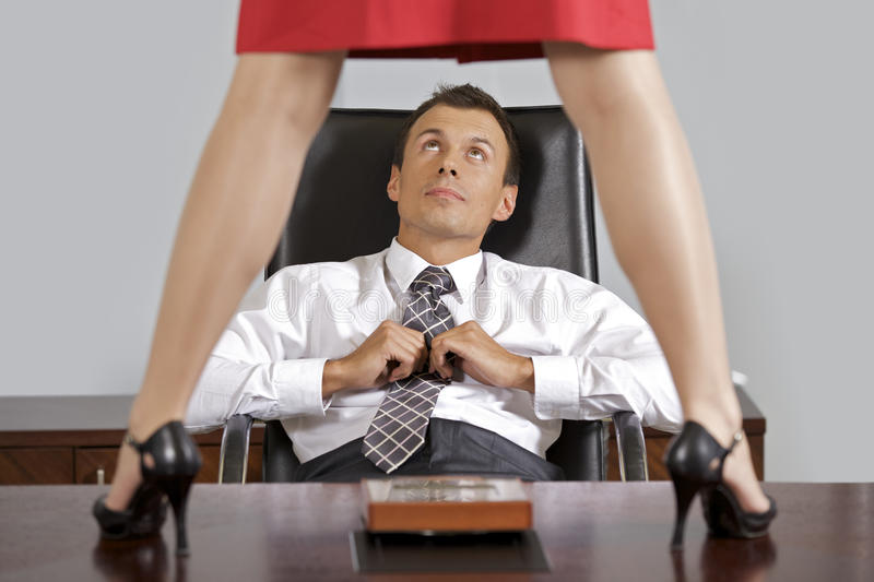 Businesswoman standing on table in front of businessman at office stock images