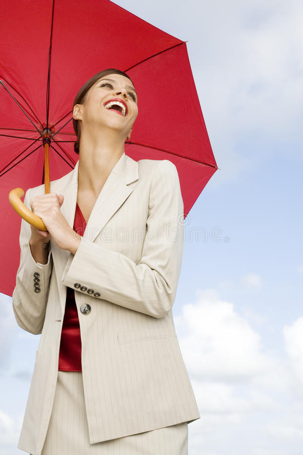 A businesswoman standing underneath an umbrella royalty free stock photography