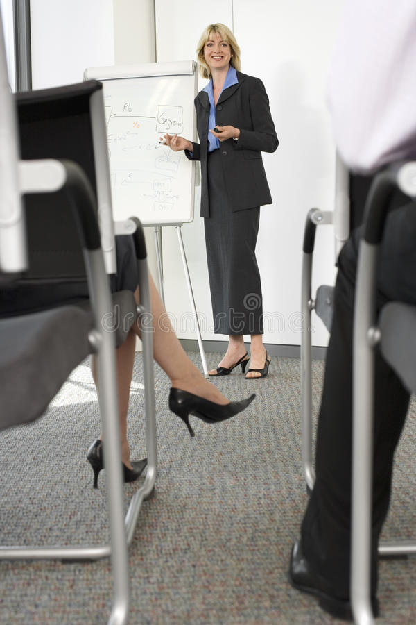 Businesswoman standing beside whiteboard in conference room, giving presentation to colleagues royalty free stock image