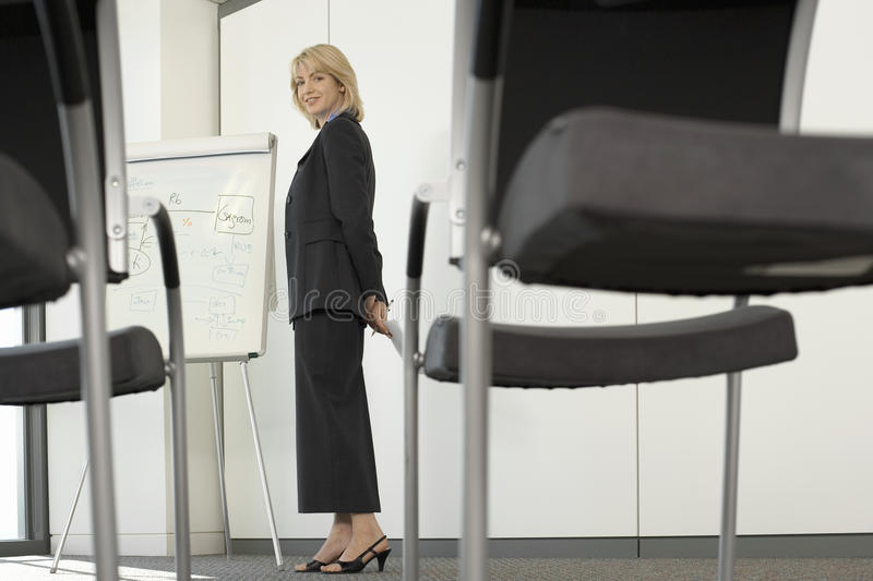 Businesswoman standing beside whiteboard in empty conference room, chairs in foreground, portrait stock photos