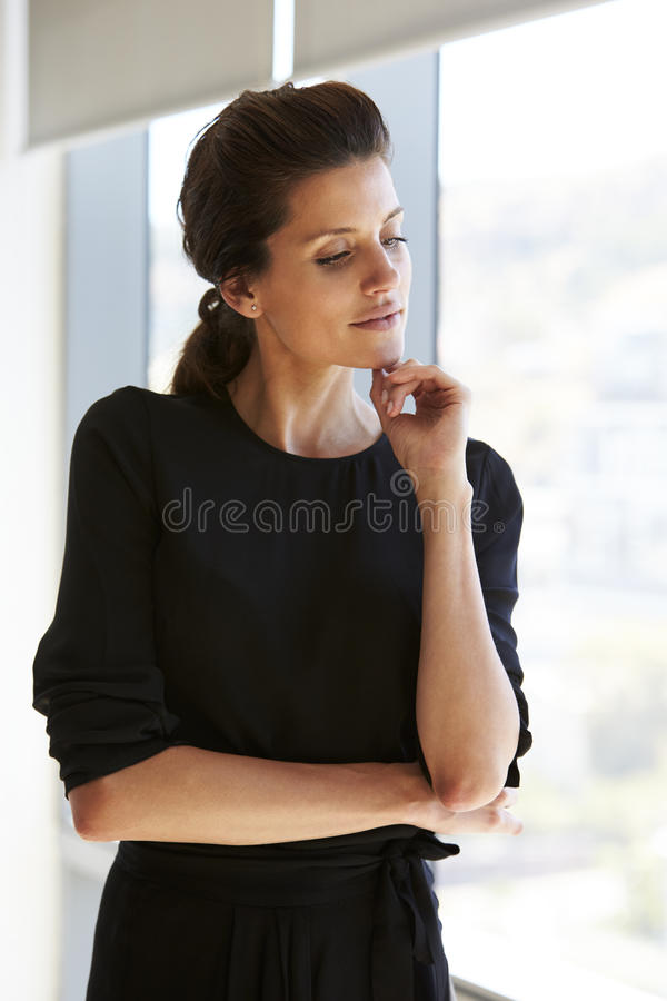Businesswoman Standing By Window In Office royalty free stock photography