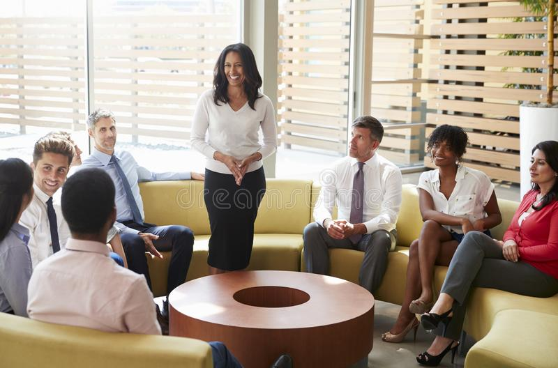 Businesswoman stands addressing colleagues in office lounge royalty free stock photography