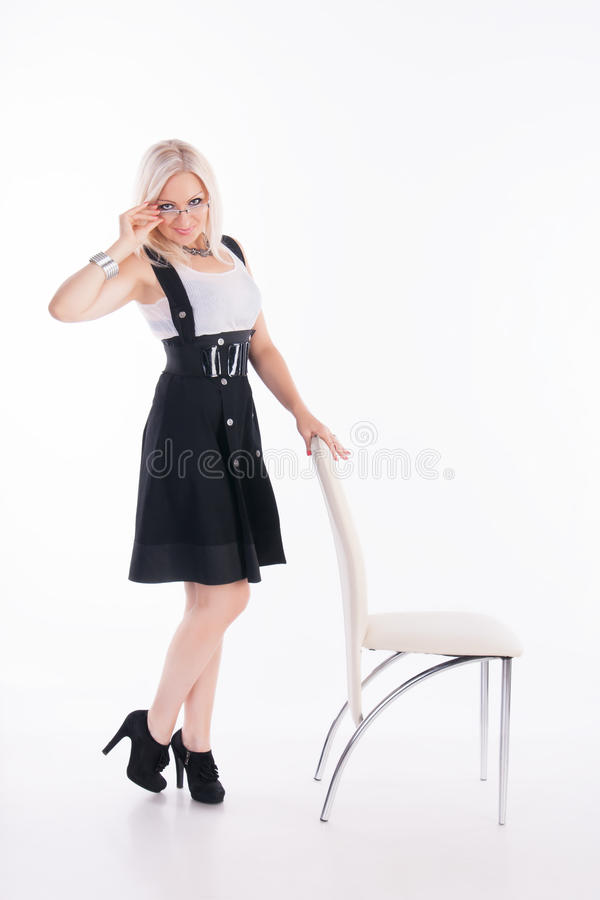 Businesswoman stands near a chair. Looking at you against the white background stock images