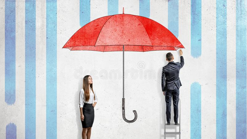 A businesswoman stands near a wall where a businessman draws a giant red umbrella covering them from the rain. stock photo