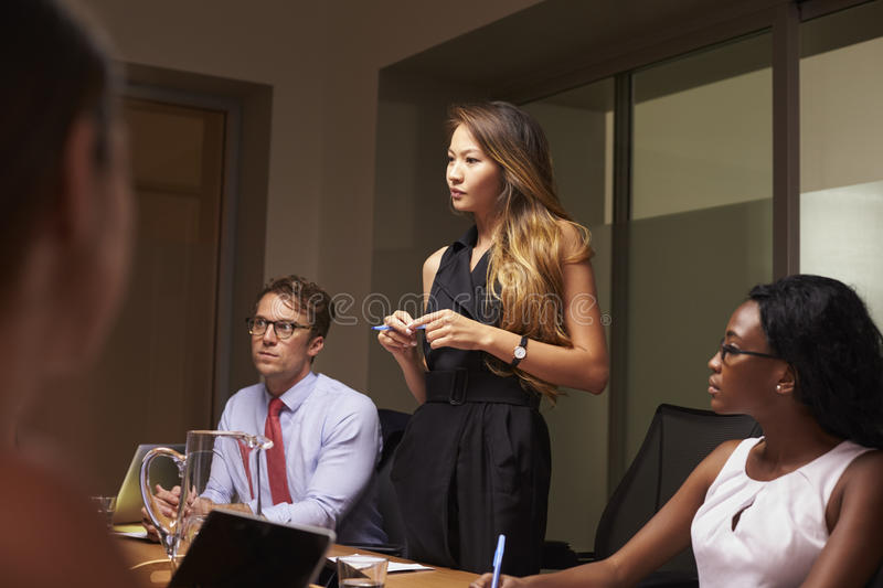 Businesswoman stands among seated team at an evening meeting royalty free stock photography