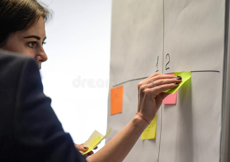 Businesswoman sticking adhesive notes on whiteboard in creative office royalty free stock photography