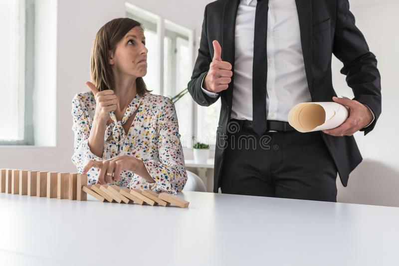 Businesswoman stopping falling dominos and showing thumbs up sign royalty free stock photography