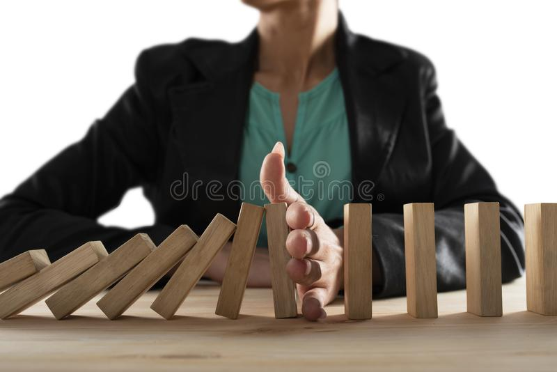 Businesswoman stops a chain fall like domino game. Concept of preventing crisis and failure in business. royalty free stock images