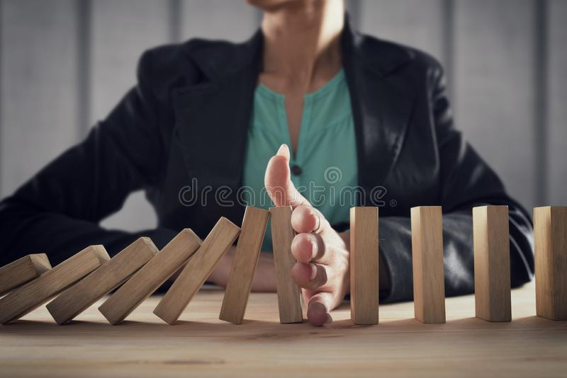 Businesswoman stops a chain fall like domino game. Concept of preventing crisis and failure in business. stock photos