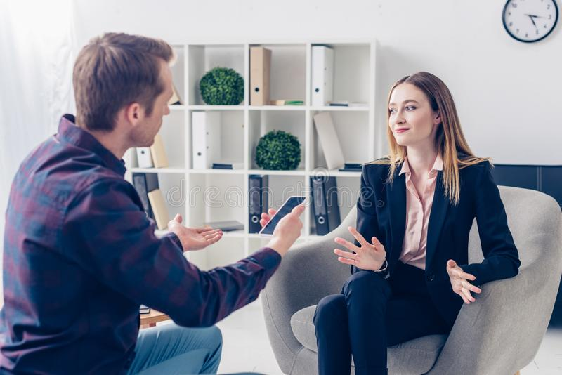 Businesswoman in suit giving interview to journalist and gesturing. In office stock photography