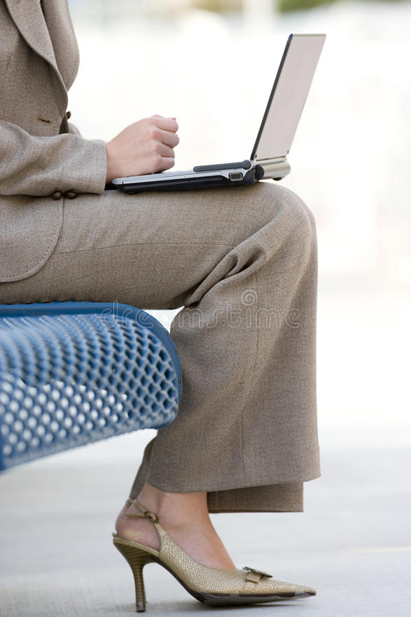 Businesswoman in suit and high heels using laptop on pavement bench, low section, profile stock image