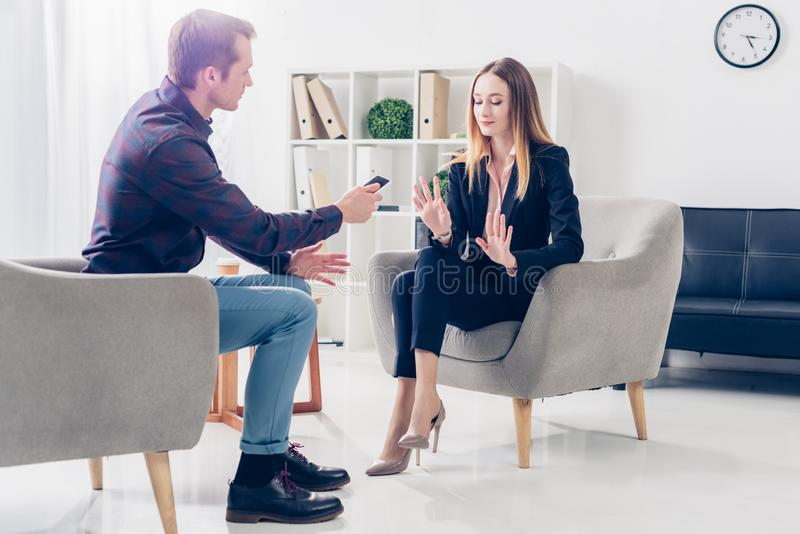 Businesswoman in suit rejecting giving interview to journalist. At workspace stock photography