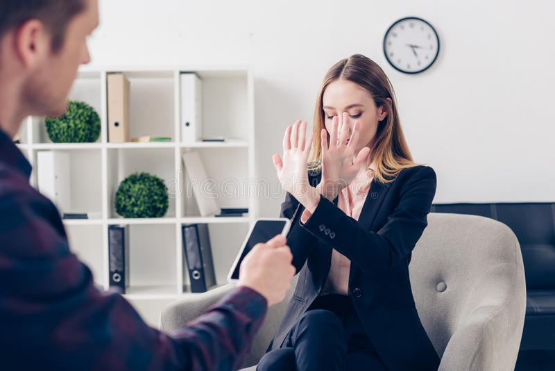 Businesswoman in suit rejecting giving interview to journalist and showing stop sign. In office stock photos