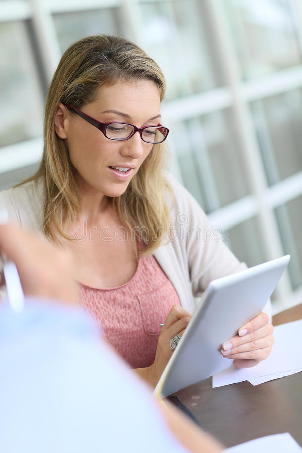 Businesswoman on a tablet during the meeting royalty free stock image