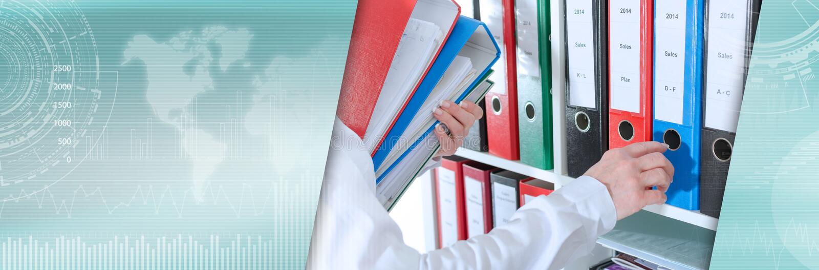 Businesswoman taking binders from a shelf; panoramic banner royalty free stock images