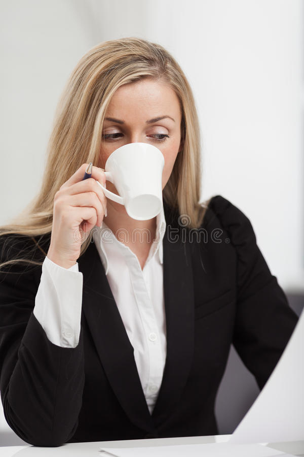 Businesswoman taking a coffee break. Enjoying a cup of hot coffee while trying to read her computer screen at the same time royalty free stock images