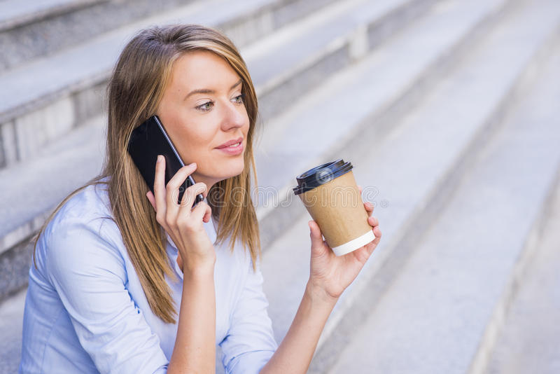 Businesswoman taking a coffee break and using smartphone. Businesswoman taking a coffee break and using smartphone royalty free stock photo