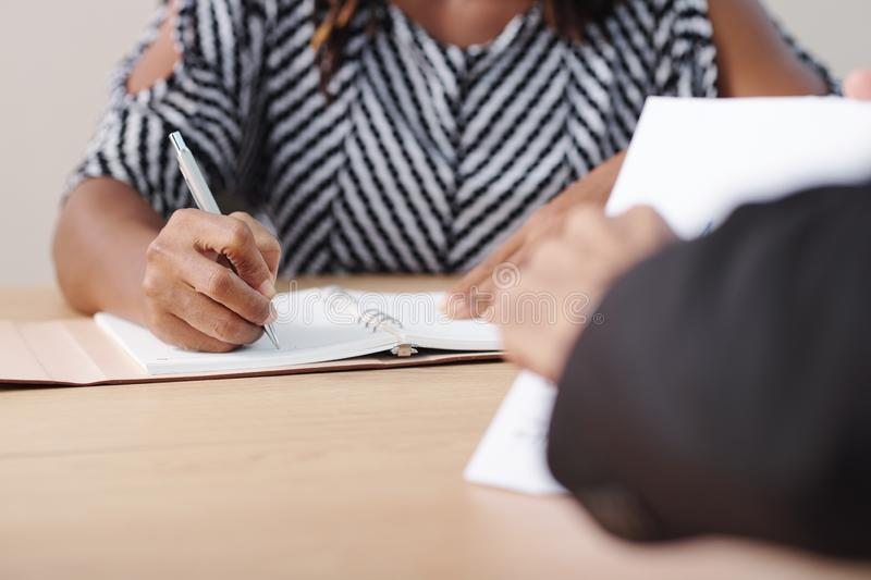 Businesswoman taking notes. In planner when listenng to coworker at meeting stock images