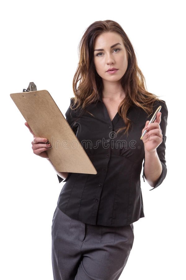 Businesswoman taking notes. Pretty brunette in a business suit poised with a clip board and a silver pen isolated on white stock photography